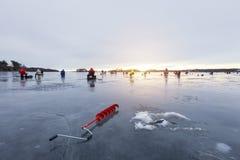 Gruppo di fishermens su pesca di inverno sul ghiaccio al tramonto fotografia stock libera da diritti