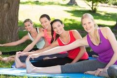 Gruppo di forma fisica che fa yoga in parco Fotografia Stock