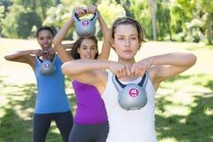 Gruppo di forma fisica che risolve nel parco con le campane del bollitore Fotografia Stock Libera da Diritti