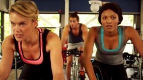 Gruppo di forma fisica che risolve sulla bici di esercizio video d archivio