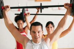 Gruppo di forma fisica con il barbell in ginnastica fotografia stock