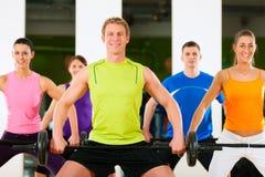 Gruppo di forma fisica con il barbell in ginnastica Immagini Stock