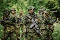 Gruppo di forze speciali dei soldati durante l'incursione nella foresta Immagine Stock