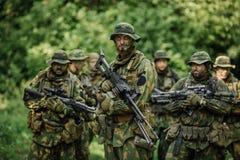 Gruppo di forze speciali dei soldati durante l'incursione nella foresta Fotografie Stock