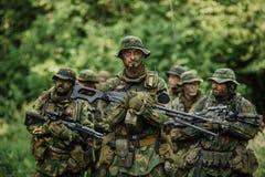 Gruppo di forze speciali dei soldati durante l'incursione nella foresta Immagini Stock