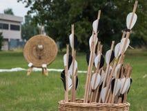 Gruppo di frecce dentro il canestro di vimini e Straw Archery Target dentro immagine stock