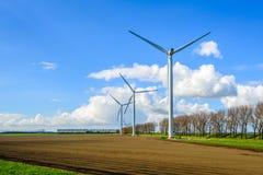 Gruppo di generatori eolici al bordo di un campo arato Fotografia Stock Libera da Diritti