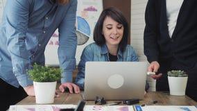 Gruppo di gente di affari che lavora e che comunica alla scrivania che esamina il computer portatile stock footage