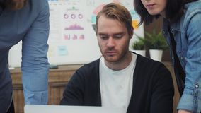 Gruppo di gente di affari che lavora e che comunica alla scrivania che esamina il computer portatile archivi video