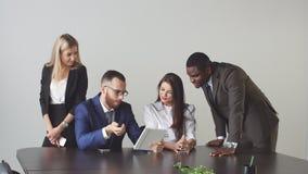 Gruppo di gente di affari che per mezzo del computer della compressa nel corso di una riunione stock footage