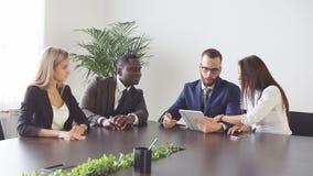 Gruppo di gente di affari che per mezzo del computer della compressa nel corso di una riunione video d archivio