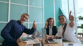 Gruppo di gente di affari felice della corsa mista che mostra i pollici su nell'ufficio 4K archivi video