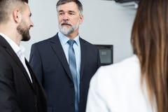 Gruppo di gente di affari occupata di concetto Gruppo di affari che discute lavoro nel corridoio dell'edificio per uffici immagine stock libera da diritti