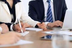 Gruppo di gente di affari alla riunione, alla fine su delle mani umane nel lavoro con la penna ed alle carte Fotografia Stock Libera da Diritti