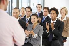 Gruppo di gente di affari che applaude altoparlante alla conclusione di una presentazione Fotografie Stock