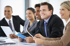Gruppo di gente di affari che ascolta il collega che indirizza riunione dell'ufficio