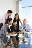 Gruppo di gente di affari che ha riunione intorno al computer A della compressa fotografie stock