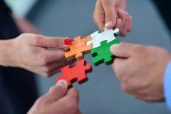 Gruppo di gente di affari che monta puzzle Immagine Stock