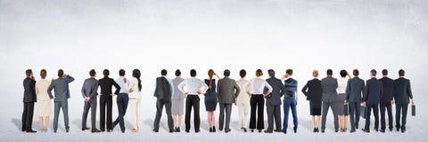 Gruppo di gente di affari che sta davanti al fondo grigio in bianco immagini stock