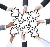 Gruppo di gente di affari che tiene i pezzi di puzzle Immagini Stock