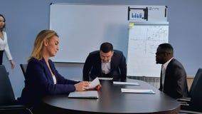 Gruppo di gente di affari che viene ad un ufficio, prendendo placec vicino allo scrittorio, preparante per una riunione Fotografia Stock Libera da Diritti