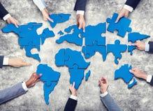 Gruppo di gente di affari con il puzzle che si forma nella mappa di mondo Fotografia Stock Libera da Diritti