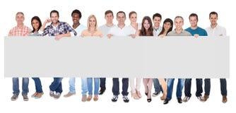 Gruppo di gente di affari con un'insegna in bianco Fotografia Stock