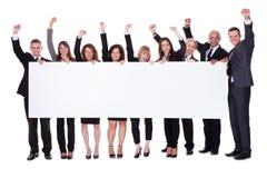 Gruppo di gente di affari con un'insegna in bianco immagini stock libere da diritti