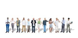 Gruppo di gente di affari multietnica che per mezzo dei dispositivi di Digital Immagine Stock