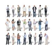 Gruppo di gente di affari multietnica che per mezzo dei dispositivi di Digital immagine stock libera da diritti