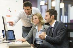 Gruppo di gente di affari in una riunione all'ufficio, funzionamento sui comp. Immagini Stock