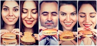 Gruppo di gente felice che mangia i cheeseburger immagine stock