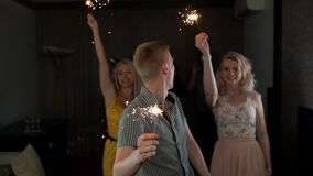 Gruppo di gente felice con le stelle filante maschii della tenuta dell'intestazione al dancing ed a sorridere del partito archivi video