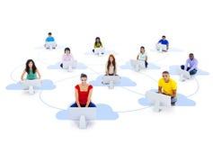 Gruppo di gente Multi-etnica collegata che si siede su una nuvola Immagini Stock