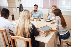Gruppo di gente multirazziale che studia con i libri nella biblioteca di istituto universitario immagini stock