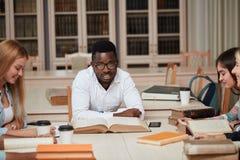 Gruppo di gente multirazziale che studia con i libri nella biblioteca di istituto universitario fotografia stock libera da diritti