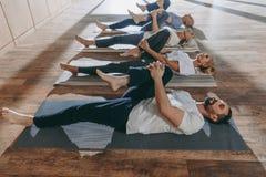 gruppo di gente senior che allunga in stuoie di yoga fotografia stock libera da diritti