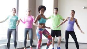 Gruppo di gente sorridente che balla nella palestra o nello studio stock footage