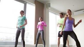 Gruppo di gente sorridente che balla nella palestra o nello studio video d archivio