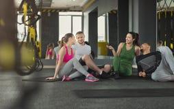Gruppo di gente sportiva che si siede sul pavimento alla palestra Fotografie Stock