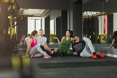 Gruppo di gente sportiva che si siede sul pavimento alla palestra Fotografie Stock Libere da Diritti