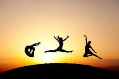Gruppo di ginnaste che saltano nel tramonto Immagine Stock Libera da Diritti