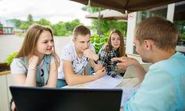 Gruppo di giovane allievo che per mezzo del computer portatile esterno Immagine Stock