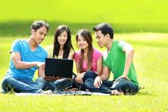 Gruppo di giovane allievo che per mezzo del computer portatile esterno Fotografia Stock