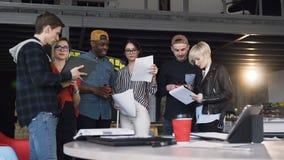 Gruppo di giovane condizione dei pantaloni a vita bassa vicino alla tavola in pieno dei documenti, computer portatile, compressa  archivi video