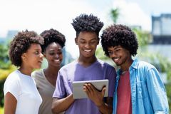 Gruppo di giovane messaggio di invio afroamericano degli adulti con la compressa digitale fotografia stock