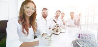 Gruppo di giovane sperimentazione dei clinici nel laboratorio di ricerca Immagini Stock Libere da Diritti