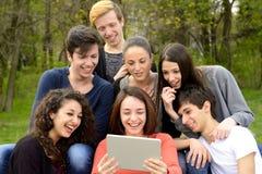 Gruppo di giovani adulti che passano in rassegna una compressa Immagine Stock