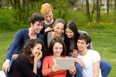 Gruppo di giovani adulti che passano in rassegna una compressa e divertiresi Fotografie Stock