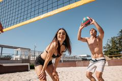 Gruppo di giovani allegri che giocano beach volley il giorno soleggiato fotografia stock libera da diritti